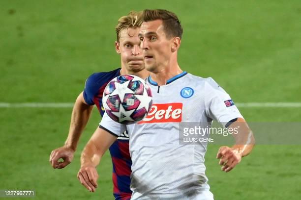Barcelona's Dutch midfielder Frenkie De Jong fights for the ball with Napoli's Polish forward Arkadiusz Milik during the UEFA Champions League round...