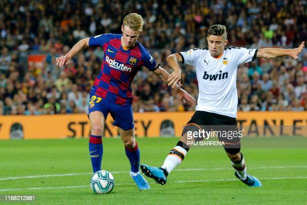 Barcelona's Dutch midfielder Frenkie De Jong vies with Valencia's Brazilian defender Gabriel Paulista during the Spanish league football match FC...