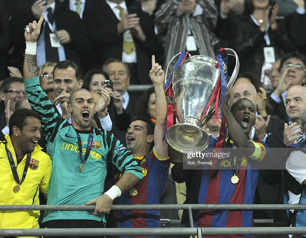 Barcelona's Eric Abidal lifts the trophy and celebrates with Xavi Hernandez and goalkeeper Victor Valdes (green shirt) after the UEFA Champions League final between FC Barcelona and Manchester United FC at Wembley Stadium on May 28, 2011 in London, England. Barcelona won the match 3-1.