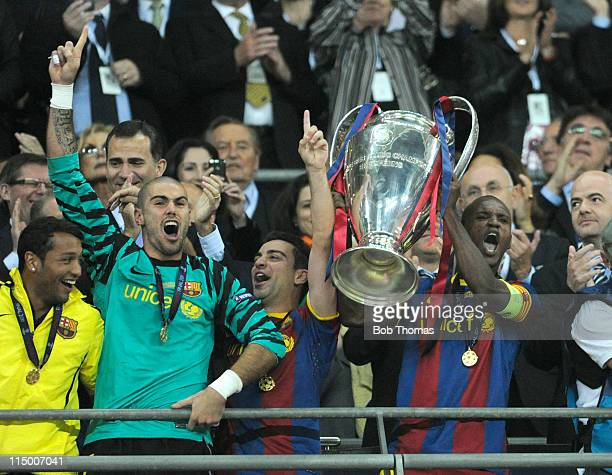 Barcelona's Eric Abidal lifts the trophy and celebrates with Xavi Hernandez and goalkeeper Victor Valdes after the UEFA Champions League final...