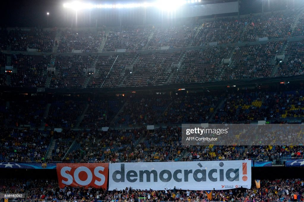 Barcelona's fans display a giant banner reading 'SOS Democracy' before the UEFA Champions League Group D football match FC Barcelona vs Juventus at the Camp Nou stadium in Barcelona on September 12, 2017. / AFP PHOTO / Josep LAGO