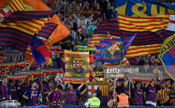 Barcelona's fans wave team's flags and cheer from the stands during the Spanish league football match between FC Barcelona and Villarreal CF at the...
