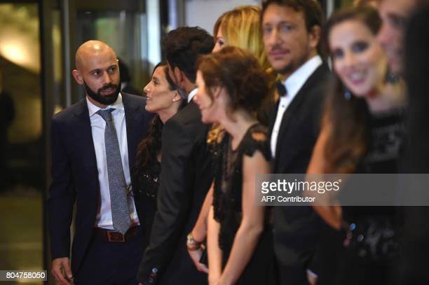 Barcelona's football player Javier Mascherano poses with other guests on a red carpet during Argentine football star Lionel Messi and Antonella...