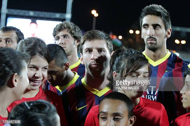 Barcelona's football player Lionel Messi and team mates pose with Palestinian children during a training session at the stadium of Dora in the West...