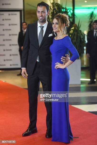 Barcelona's football player Sergio Busquets and his wife pose on a red carpet during Argentine football star Lionel Messi and Antonella Roccuzzo...