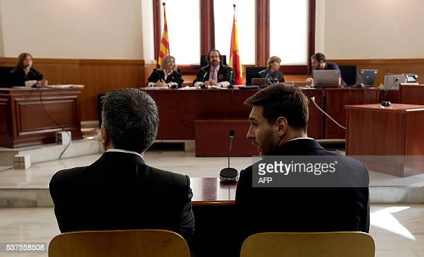 Barcelona's football star Lionel Messi and his father Jorge Horacio Messi listen as they face judges in a tax fraud case at the courthouse of...