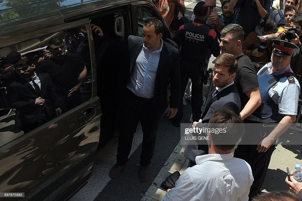 Barcelona's football star Lionel Messi (C) leaves the courthouse on June 2, 2016 in Barcelona. The 28-year-old football star was cheered and jeered as he emerged from a van accompanied by his father Jorge Horacio Messi. The two are accused of using a chain of fake companies in Belize and Uruguay to avoid paying taxes on 4.16 million euros ($4.6 million) of Messi's income earned through the sale of his image rights from 2007-09. / AFP / LLUIS
