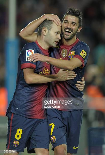 Barcelona's forward David Villa celebrates with Barcelona's midfielder Andres Iniesta after scoring during the Spanish league football match FC...