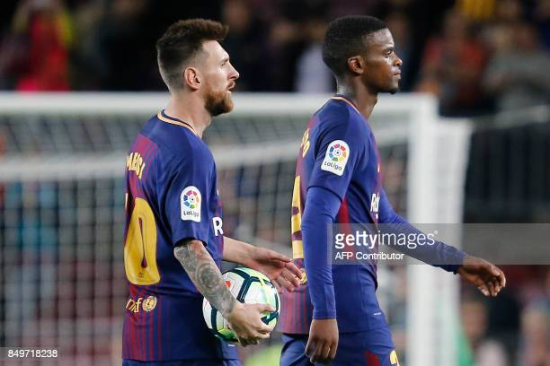 Barcelona's forward from Argentina Lionel Messi holds the ball next to Barcelona's defender from Portugal Nelson Semedo after the Spanish league...