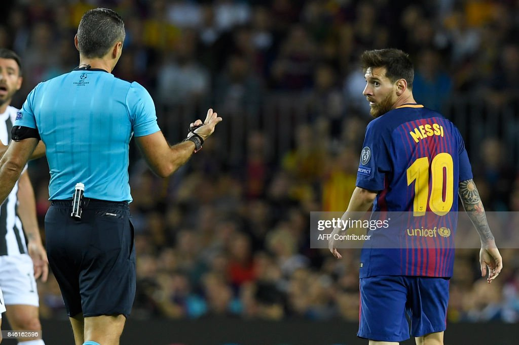Barcelona's forward from Argentina Lionel Messi (R) receives a yellow card from referee during the UEFA Champions League Group D football match FC Barcelona vs Juventus at the Camp Nou stadium in Barcelona on September 12, 2017. /