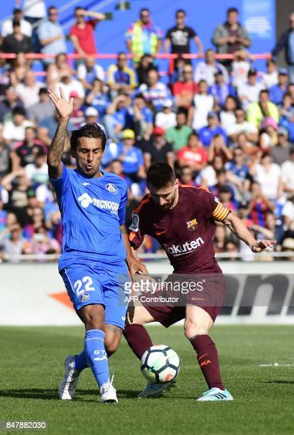 Barcelona's forward from Argentina Lionel Messi vies with Getafe's defender from Uruguay Damian Suarez during the Spanish league football match...