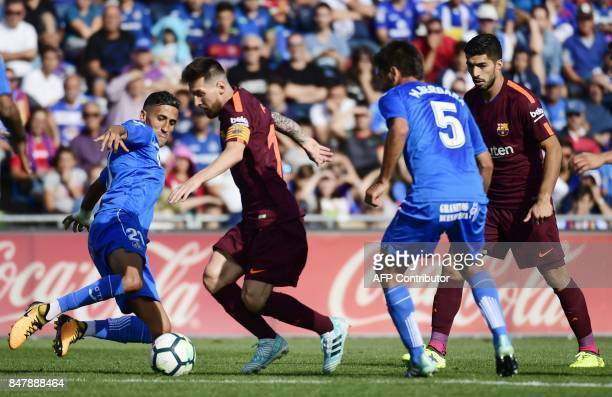 Barcelona's forward from Argentina Lionel Messi vies with Getafe's midfielder from Morocco Faycal Fajr during the Spanish league football match...