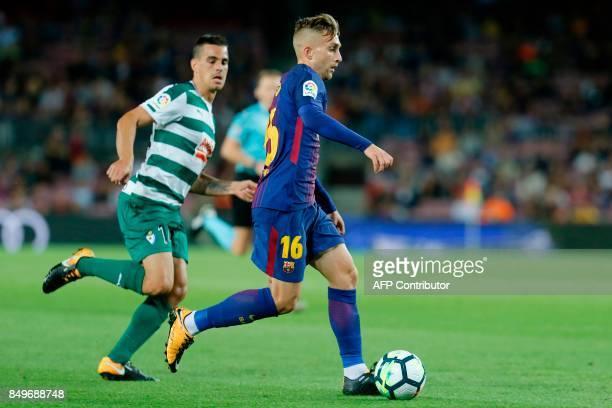 Barcelona's forward from Spain Gerard Deulofeu runs with the ball besides Eibar's midfielder from Spain Dani Garcia during the Spanish league...
