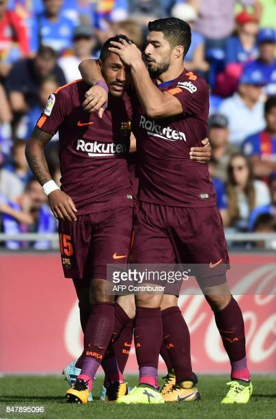 Barcelona's forward from Uruguay Luis Suarez congratulates Barcelona's midfielder from Brazil Paulinho after scoring a goal during the Spanish league...