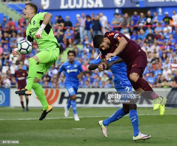Barcelona's forward from Uruguay Luis Suarez falls down after clashing with Getafe's goalkeeper from Spain Vicente Guaita during the Spanish league...