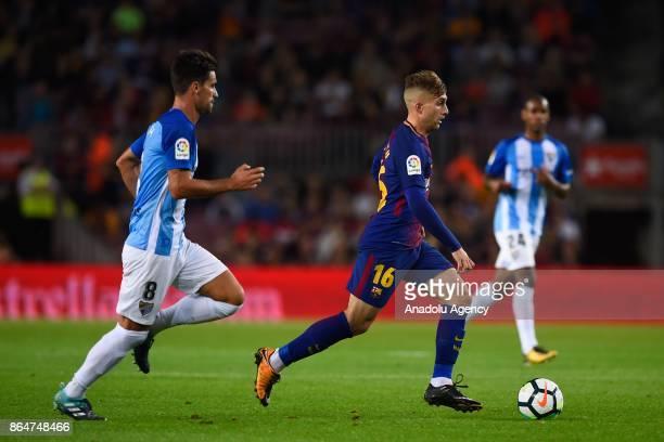 Barcelona's forward Gerard Deulofeu vies with Malaga's midfielder Adrian Gonzalez during the Spanish league football match FC Barcelona vs Malaga CF...