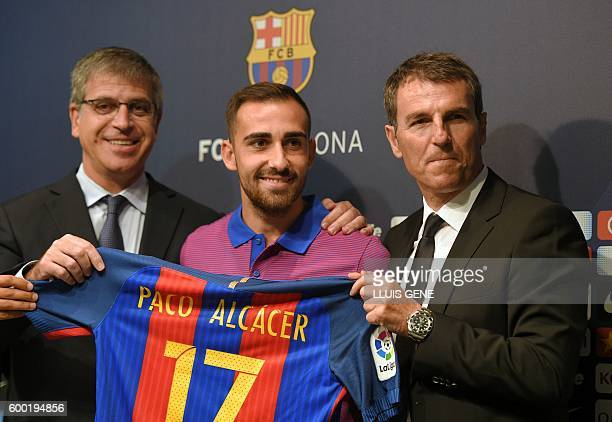 FC Barcelona's forward Paco Alcacer poses with his new jersey flanked by Barcelona's third VicePresident Jordi Mestre and Barcelon's general manager...