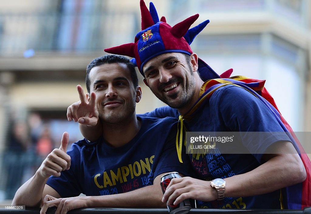 Barcelona's forward Pedro Rodriguez (L) and Barcelona's forward David Villa pose as they and their teammates parade on a bus through a crowd of supporters celebrating in the streets of Barcelona on May 13, 2013, two days after their team won the Spanish league. The Catalans didn't even need to set foot on the pitch to seal the title on May 11 as Real Madrid's 1-1 draw with Espanyol meant Barca had already been crowned champions before their 2-1 win over Atletico Madrid on May 12, 2013.