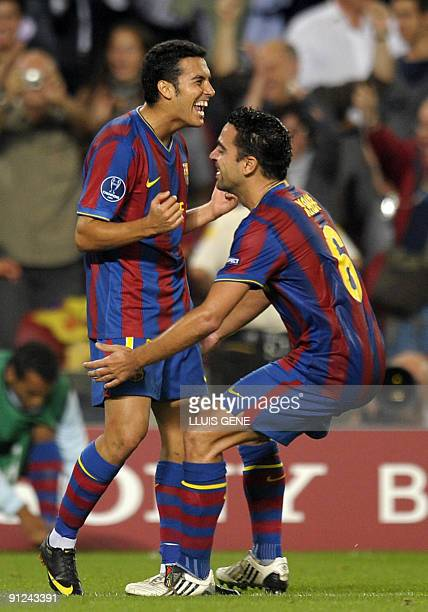 Barcelona's forward Pedro Rodriguez celebrates with teammate midfielder Xavi Hernandez after scoring a goal during the UEFA Champions League football...