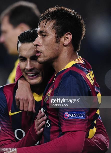 Barcelona's forward Pedro Rodriguez is congratulated by his teammate Barcelona's Brazilian forward Neymar da Silva Santos Junior after scoring during...