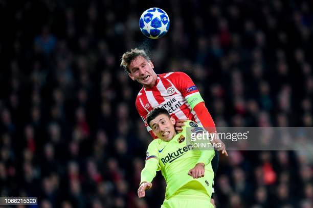 Barcelona's French defender Clement Lenglet and Eindhoven's forward Luuk De Jong jump for the ball during the UEFA Champions League football match...