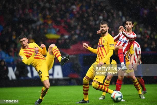 Barcelona's French defender Clement Lenglet, Barcelona's Spanish defender Gerard Pique and Atletico Madrid's Portuguese forward Joao Felix eye the...