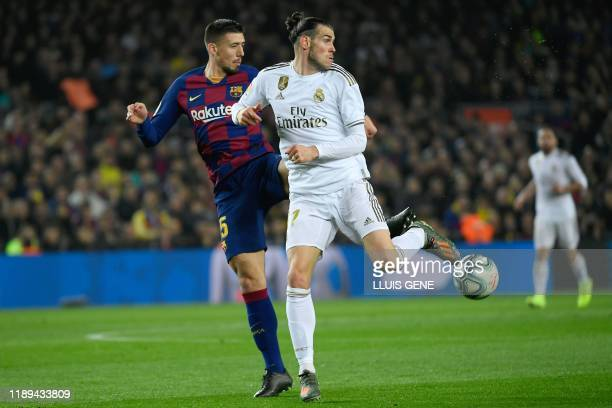 Barcelona's French defender Clement Lenglet challenges Real Madrid's Welsh forward Gareth Bale during the El Clasico Spanish League football match...