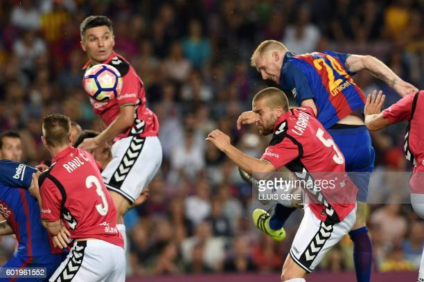 Barcelona's French defender Jeremy Mathieu heads the ball to score a goal beside Deportivo Alaves' defender Laguardia during the Spanish league...