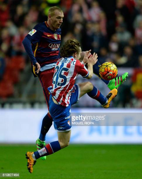 Barcelona's French defender Jeremy Mathieu jumps for the ball with Sporting Gijon's Croatian forward Alen Alilovic during the Spanish league football...