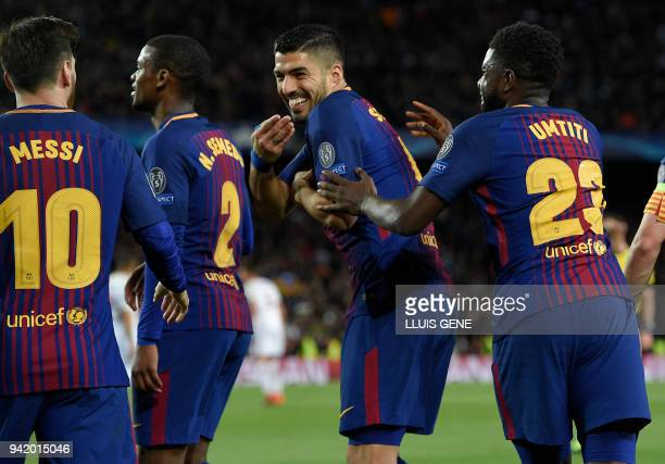 Barcelona's French defender Samuel Umtiti and Barcelona's Uruguayan forward Luis Suarez celebrate Roma's second owngoal during the UEFA Champions...