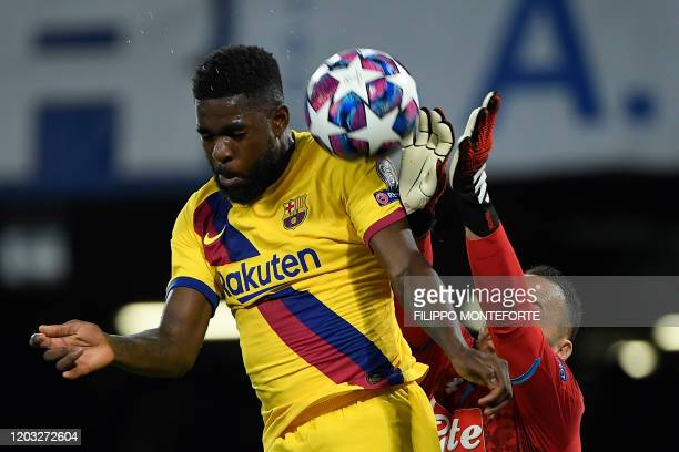 TOPSHOT Barcelona's French defender Samuel Umtiti jumps for the ball with Napoli's Colombian goalkeeper David Ospina during the UEFA Champions League...