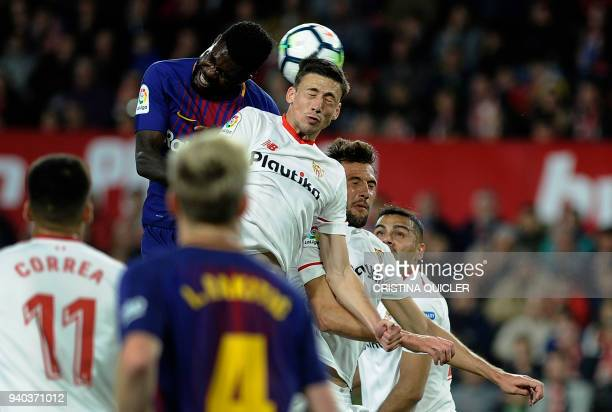 Barcelona's French defender Samuel Umtiti jumps for the ball with Sevilla's French defender Clement Lenglet during the Spanish League football match...