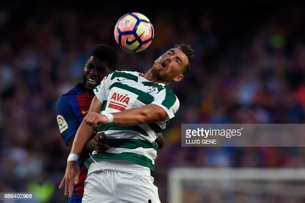 Barcelona's French defender Samuel Umtiti vies with Eibar's forward Sergi Enrich during the Spanish league football match FC Barcelona vs SD Eibar at...