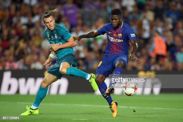 Barcelona's French defender Samuel Umtiti vies with Real Madrid's Welsh forward Gareth Bale during the Spanish Supercup first leg football match FC...