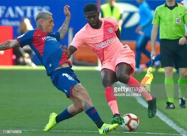 Barcelona's French defender Samuel Umtiti vies with SD Huesca's Argentinian forward Chimy Avila during the Spanish league football match between SD...