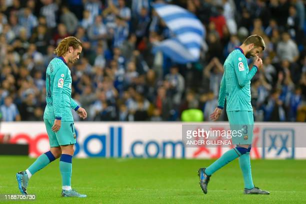 Barcelona's French forward Antoine Griezmann and Barcelona's Spanish defender Gerard Pique react at the end of the Spanish league football match...