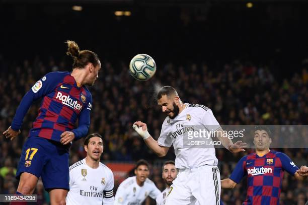 Barcelona's French forward Antoine Griezmann and Real Madrid's French forward Karim Benzema head the ball during the El Clasico Spanish League...