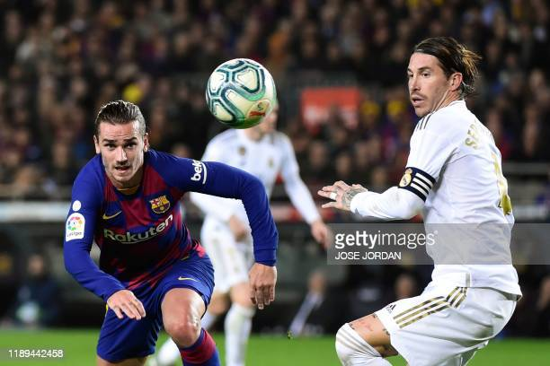 TOPSHOT Barcelona's French forward Antoine Griezmann and Real Madrid's Spanish defender Sergio Ramos eye the ball during the El Clasico Spanish...