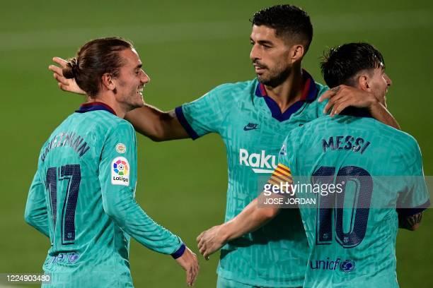 Barcelona's French forward Antoine Griezmann celebrates with Barcelona's Argentine forward Lionel Messi and Barcelona's Uruguayan forward Luis Suarez...