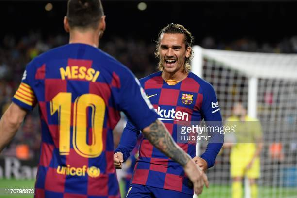 Barcelona's French forward Antoine Griezmann is congratulated by teammate Barcelona's Argentine forward Lionel Messi after scoring the first goal...