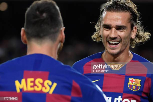 TOPSHOT Barcelona's French forward Antoine Griezmann is congratulated by teammate Barcelona's Argentine forward Lionel Messi after scoring the first...