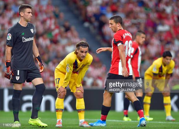 TOPSHOT Barcelona's French forward Antoine Griezmann stands between Athletic Bilbao's Spanish goalkeeper Unai Simon and Athletic Bilbao's Spanish...