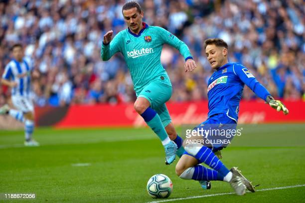 Barcelona's French forward Antoine Griezmann vies with Real Sociedad's Spanish goalkeeper Alejandro Remiro during the Spanish league football match...