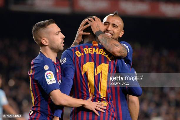 Barcelona's French forward Ousmane Dembele celebrates scoring the opening goal with Barcelona's Chilean midfielder Arturo Vidal and Barcelona's...