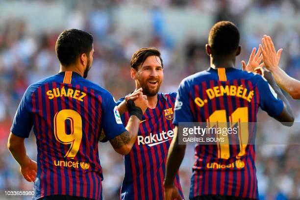 Barcelona's French forward Ousmane Dembele celebrates with Barcelona's Argentinian forward Lionel Messi and Barcelona's Uruguayan forward Luis Suarez...