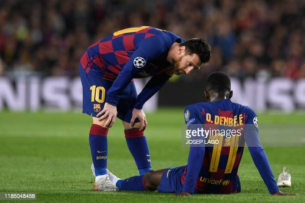 Barcelona's French forward Ousmane Dembele is conforted by Barcelona's Argentine forward Lionel Messi after an injury during the UEFA Champions...