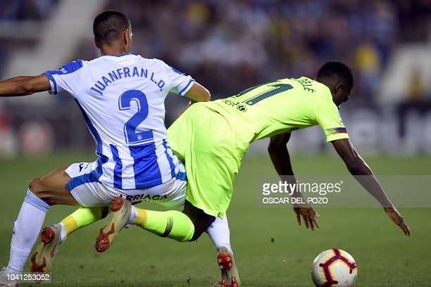 Barcelona's French forward Ousmane Dembele is tackled by Leganes' Spanish defender Juanfran during the Spanish league football match Club Deportivo...