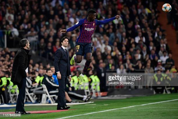 Barcelona's French forward Ousmane Dembele jumps close to Barcelona's Spanish coach Ernesto Valverde and Real Madrid's Argentinian coach Santiago...