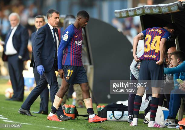Barcelona's French forward Ousmane Dembele leaves the pitch after resulting injured during the Spanish league football match between RC Celta de Vigo...