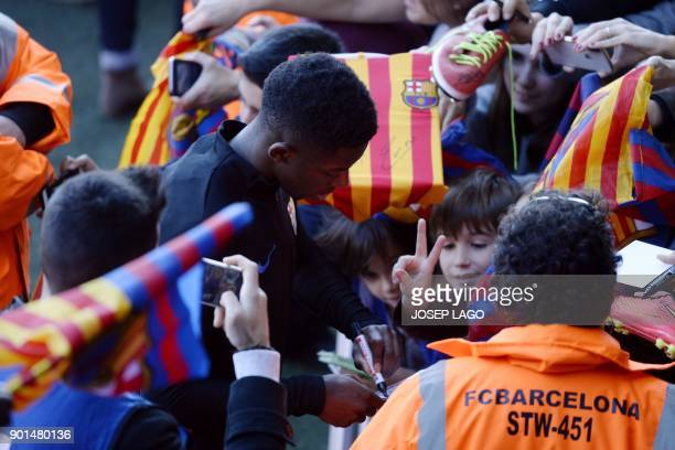 Barcelona's French forward Ousmane Dembele signs autographs for supporters at the end of a training session in Barcelona on January 5 2018 / AFP...